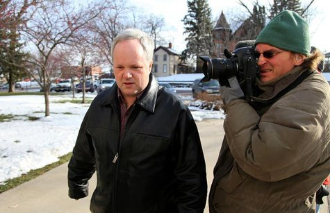William Melchert-Dinkel (L) is photographed by a news cameraman as he walks to the Rice County Courthouse to enter a not guilty plea in a ca