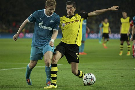 Zenit St Petersburg's Tomas Hubocan (L) is tackled by Borussia Dortmund's Robert Lewandowski during their Champions League round of 16 secon