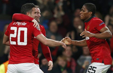 Manchester United's Robin van Persie (L) celebrates with Wayne Rooney and Antonio Valencia (R) a second goal against Olympiakos during their