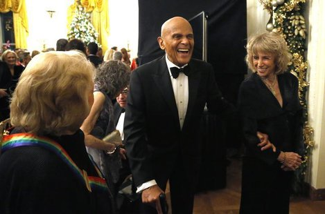 Harry Belafonte (C) laughs with a fellow audience member as they depart after a reception for the 2013 Kennedy Center Honors recipients at t