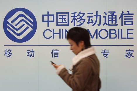 A woman looks at the screen of her mobile phone while walking past a China Mobile sign in downtown Shanghai December 18, 2013 file photo. RE