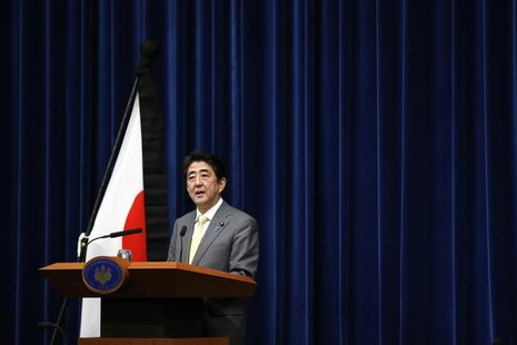 Japan's Prime Minister Shinzo Abe speaks next to the Japanese national flag, attached with a black ribbon to mourn victims during a news con