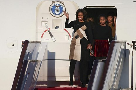 U.S. first lady Michelle Obama (L) waves as she walks out the plane with her daughters Sasha (2nd R) and Malia (R) upon their arrival at Bei
