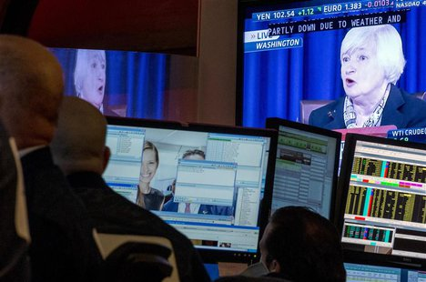 A screen displays a news conference by Federal Reserve Chair Janet Yellen as traders work on the floor of the New York Stock Exchange March