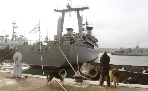 A man looks at the Ukrainian ship Slavutich (C) blocked by two Russian ships at the harbour in Sevastopol, March 20, 2014. REUTERS/Vasily Fe