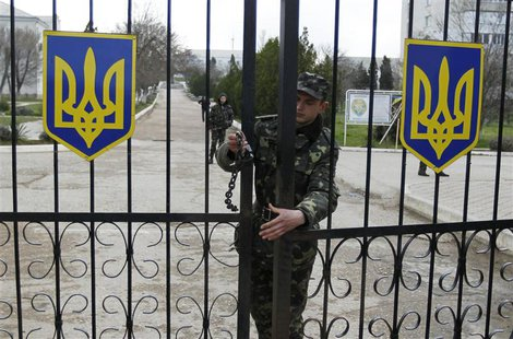 A Ukrainian soldier closes an entrance gate at the airforce base in the Crimean town of Belbek March 20, 2014. REUTERS/Shamil Zhumatov