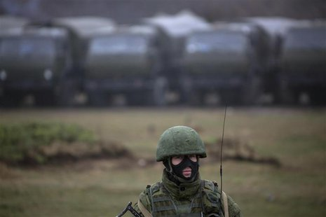 An armed man, believed to be a Russian serviceman, stands guard near a military base in Perevalnoye, near the Crimean city of Simferopol, Ma