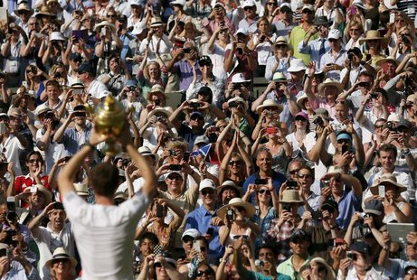 Andy Murray of Britain holds the winners trophy up to the spectators after defeating Novak Djokovic of Serbia in their men's singles final t