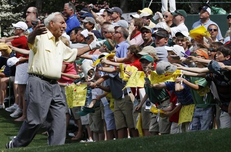 Golf great Arnold Palmer reacts to the fans during the Par 3 contest before the 2010 Masters golf tournament at the Augusta National Golf Cl