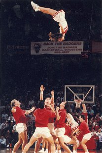 A cheerleader is vaulted into the air during halftime at a University of Wisconsin--Madison basketball game. Photograph by Greg Anderson, February 20, 1992 By uwdigitalcollections (Cheerleader toss) [CC-BY-2.0 (http://creativecommons.org/licenses/by/2.0)], via Wikimedia Commons
