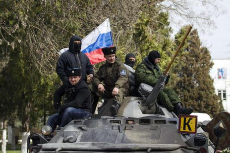 Pro-Russian supporters sit on top of a Ukrainian APC after breaking into the territory of the naval headquarters in Sevastopol, March 19, 2014.