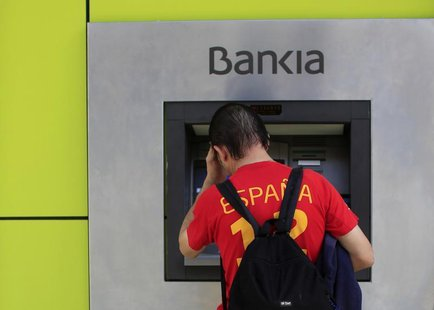A man uses an ATM machine at a Bankia bank branch in the Andalusian capital of Seville, southern Spain October 28, 2013. REUTERS/Marcelo del