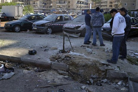 Civilians inspect a site of a roadside bomb, that exploded when the army was patrolling overnight the area in Tripoli, northern Lebanon Marc