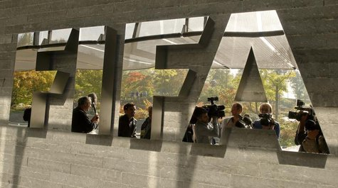 Journalists are reflected in a logo at the FIFA headquarters after a meeting of the executive committee in Zurich October 4, 2013. REUTERS/A