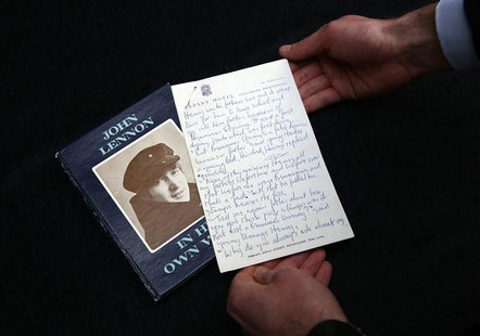 A manuscript written by John Lennon entitled 'Henry and Harry' is held for the cameras by a Sotheby's employee, London March 21, 2014. REUTE