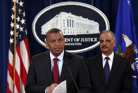 U.S. Transportation Secretary Anthony Foxx (L) and Attorney General Eric Holder hold a news conference at the Justice Department in Washingt