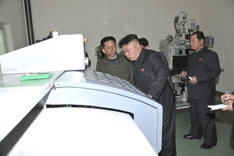 North Korean leader Kim Jong Un (C) provides field guidance during a visit to a machine plant managed by Kang Thae Ho in this undated photo