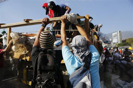 Anti-government protesters unload debris from a truck to build a barricade along a highway during a protest against Nicolas Maduro's governm