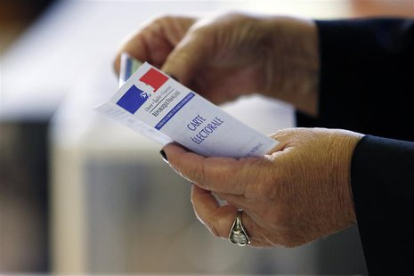 A woman holds an electoral card at a polling station in Paris March 23, 2014. REUTERS/Gonzalo Fuentes
