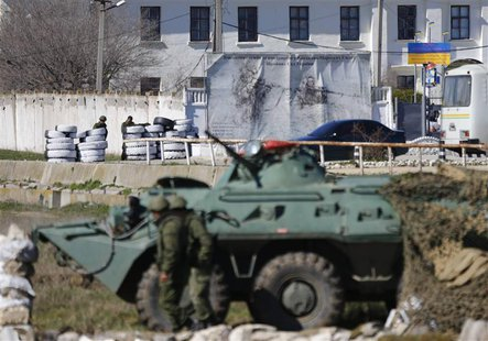 Armed men, believed to be Russian servicemen, stand guard in front of a Ukrainian marine base in the Crimean port city of Feodosia March 23,