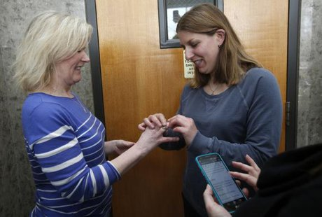 Two women exchange rings during their wedding ceremony in the hallway of the Oakland County Courthouse as the woman officiating the wedding reads the marriage vows from her cell phone.  Michigan March 22, 2014. Credit: Reuters/Rebecca Cook