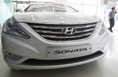 An employee walks past Hyundai Motor's Sonata, on display at the automaker's dealership in Seoul September 1, 2011. REUTERS/Truth Leem