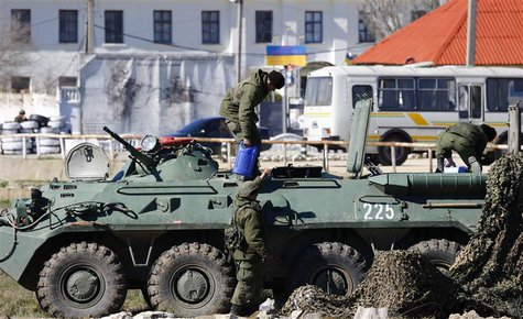 Armed men, believed to be Russian servicemen, supply an armoured personnel carrier (APC) in front of a Ukrainian marine base in the Crimean