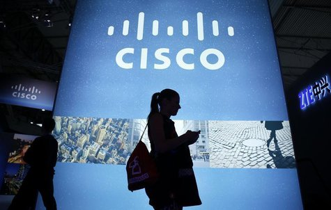 A visitor walks past a Cisco advertising panel as she looks at her mobile phone at the Mobile World Congress in Barcelona February 27, 2014.