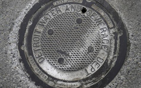 A City of Detroit Water and Sewerage man-hole cover is seen along Jefferson Avenue in the Delray neighborhood of Detroit, Michigan December