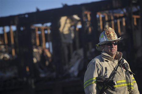A firefighter stands in front of the charred remains of the Mariner's Cove Inn in Point Pleasant Beach, New Jersey, March 21, 2014. REUTERS/