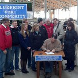Gov. Scott Walker signs a half-billion dollar property and income tax bill at Horsens Homestead Farms near Cecil, March 24, 2014. (Photo from: FOX 11).