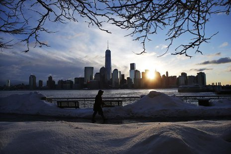 The New York skyline and the One World Trade Center are seen in the distance as a man makes his commute after a night of snow from New York