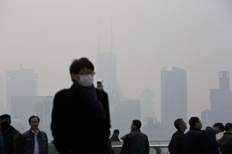 A man wearing a face mask walks through the Lujiazui financial district of Pudong on a hazy day in Shanghai, March 10, 2014. REUTERS/Aly Son