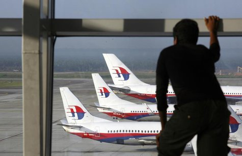 A traveller stands at the viewing gallery overlooking Malaysian Airline System (MAS) aircrafts at Kuala Lumpur International Airport in Sepa