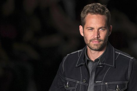 U.S. actor Paul Walker presents a creation from Colcci's 2013/2014 summer collection during Sao Paulo Fashion Week in this March 21, 2013 fi