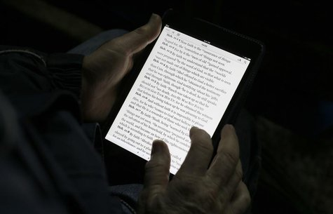 "A man reads the bible from an iPad mini at the ""Christ is the Answer International Ministries"" group's camp near Florence February 2, 2013."