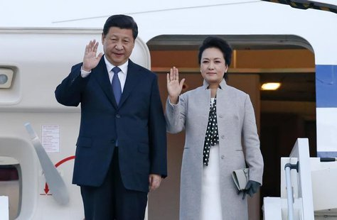 China's President Xi Jinping (L) and his wife Peng Liyuan wave as they arrive at the Lyon-Saint-Exupery airport in Colombier-Saugnieu, near