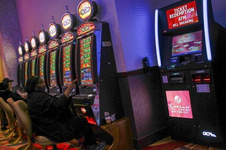 People play at slot machines inside Resorts World Casino, owned by Malaysian gaming company Genting, in the Queens borough of New York, Nove