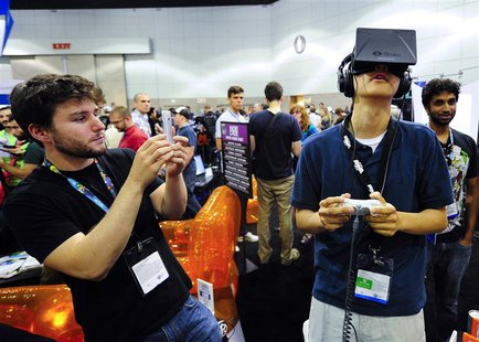 "Software designer Julian Kantor (L), who created ""The Recital"", takes a picture of Jonathan Feng using the Oculus Rift virtual reality heads"
