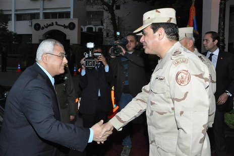 Egypt's interim President Adly Mansour (L) shakes hands with Egypt's army chief Field Marshal Abdel Fattah al-Sisi (R), after his meeting wi