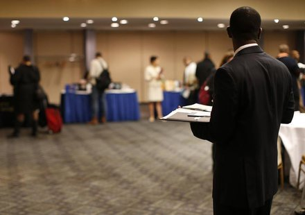 A job seeker stands in a room of prospective employers at a career fair in New York City, October 24, 2012. REUTERS/Mike Segar