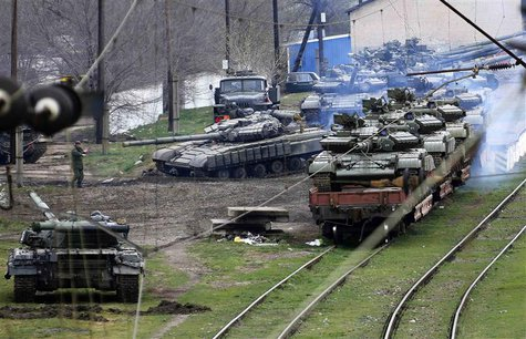 A Russian soldier (L) guides a Ukrainian tank, which is to be loaded onto a train, in northern Crimea March 27, 2014. REUTERS/Yannis Behraki