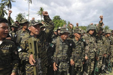 Moro Islamic Liberation Front (MILF) forces raise their fists during a show of force inside the camp in Camp Darapanan, Maguindanao province