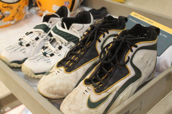 The cleats in the forefront are game worn by Brett Favre