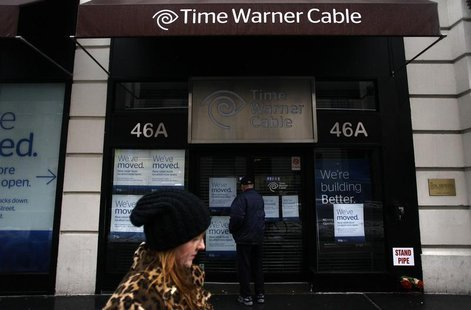 A woman walks past the old Time Warner Cable headquarters as a man tries to enter the building in New York February 13, 2014. REUTERS/Joshua