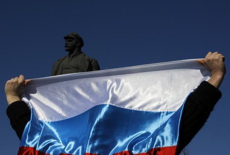 A pro-Russian activist lifts a Russian flag in front of a statue of Lenin during a rally in Donetsk's Lenin square March 23, 2014. REUTERS/Y