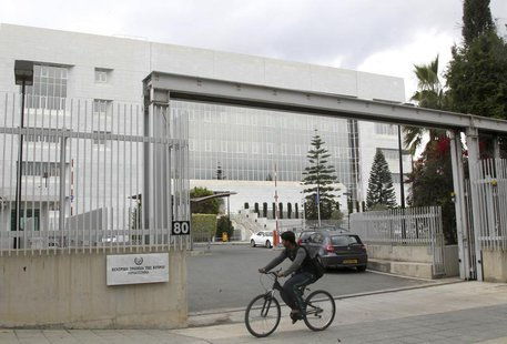 A man cycles pass the Central Bank of Cyprus on the island's capital Nicosia, April 18, 2013. REUTERS/Andreas Manolis