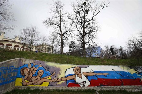 Graffiti depicting Russian President Vladimir Putin (R) extending a hand to the Ukrainian people is seen on a wall in the Crimean city of Si