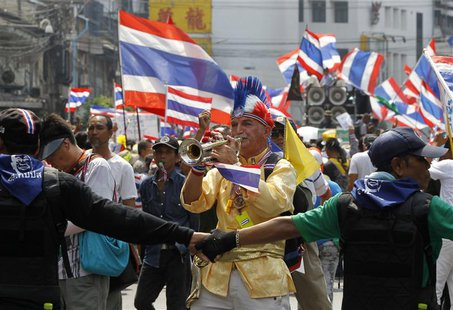 An anti-government protester blows a trumpet during a rally in central Bangkok March 28, 2014. REUTERS/Chaiwat Subprasom