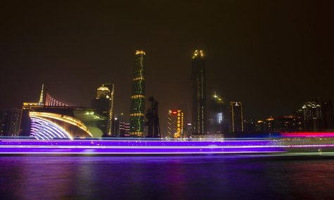 A long exposure picture of boats passing by a business area along the Pearl River in Guangzhou, Guangdong province, March 22, 2014. REUTERS/